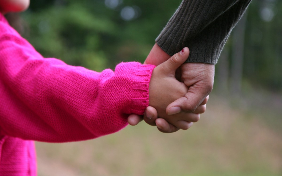 childs hand holding an adult hand