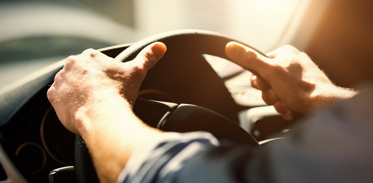 Person driving with hands on the steering wheel