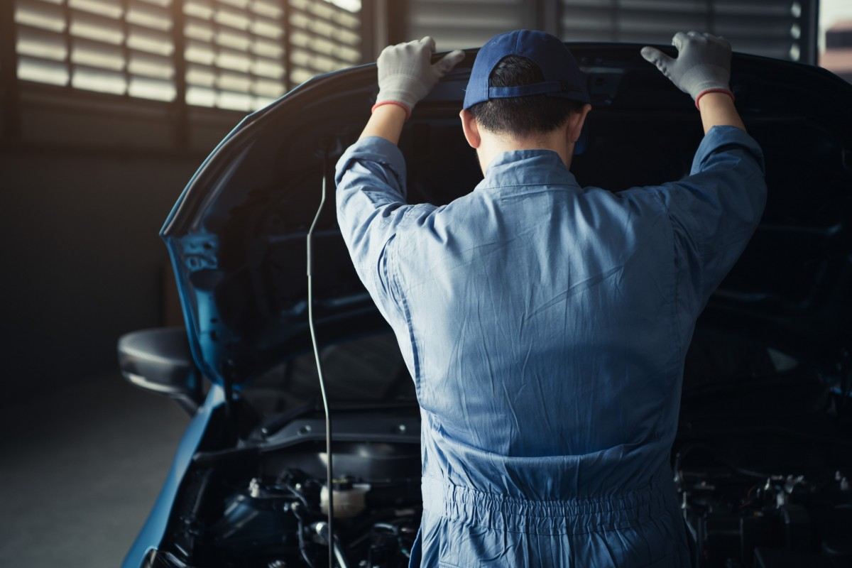 mechanic with hood up and looking at car